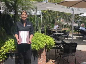 Employees outside holding menu, smiling in front of patio
