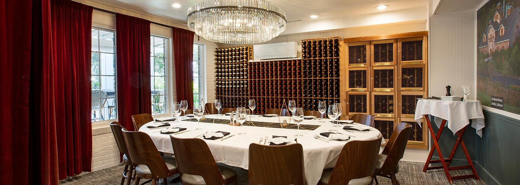 Private dining room and wine cellar with service set for 12 at oval table.