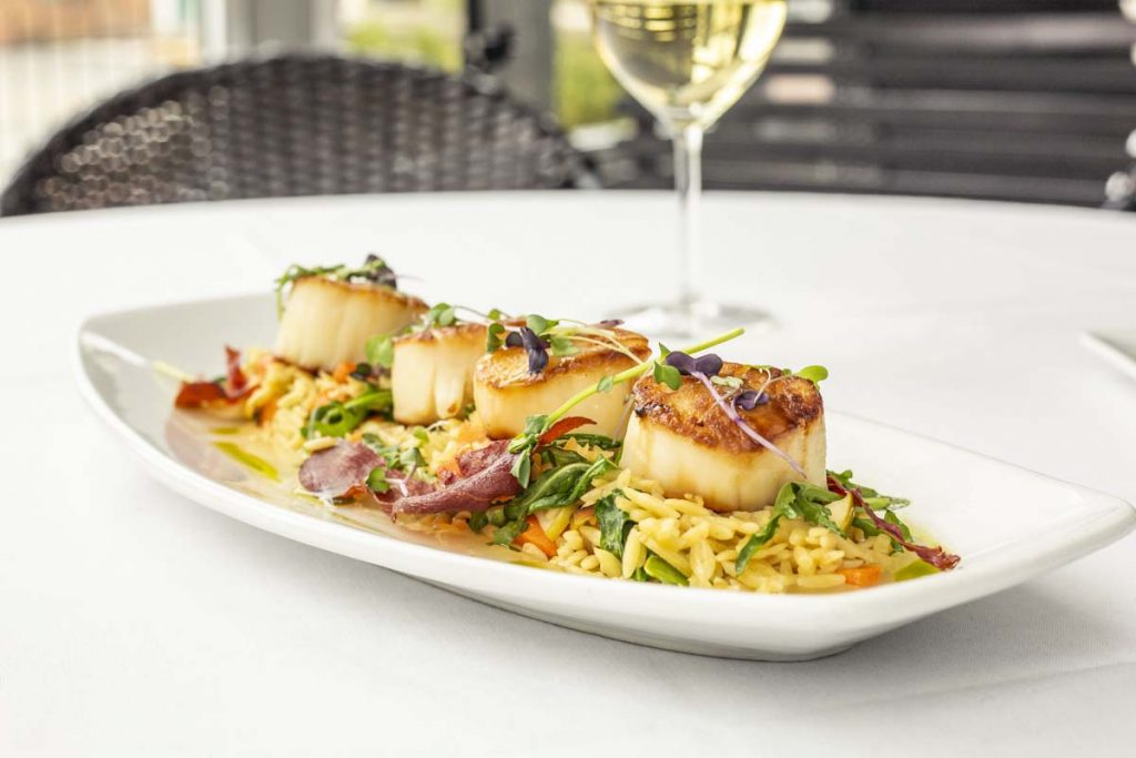 Tucci's jumbo pan-seared scallops on bed of orzo pasta with white wine in background