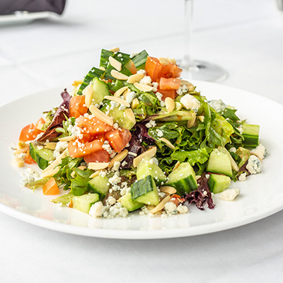 Plated chopped salad with tomatoes, grated cheese.